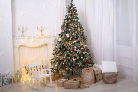 Christmas decorations gift boxes in wrapping paper near Christmas tree. Stok Fotoğraf