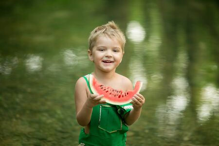 A handsome boy with a watermelon in his hands. Stok Fotoğraf