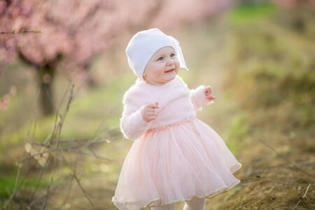Little princess Toddler dressed in a pink dress walks in the fresh air and enjoys life Stok Fotoğraf