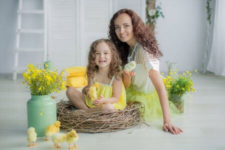 Family photo of mom and daughter in yellow bright dresses against a white wall.