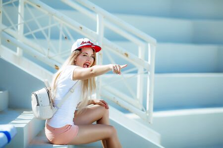 The young woman actively spends time on the sports podium and supports her favorite team. Stok Fotoğraf