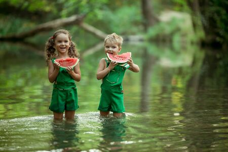 Children play in the water and take a bite of juicy colorful ripe watermelon.