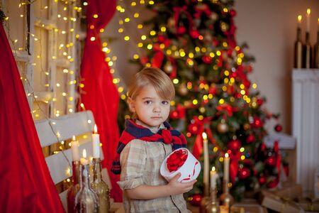 Boy 4-6 years old in a red festive room and a beautiful hairstyle on new years eve. Stok Fotoğraf