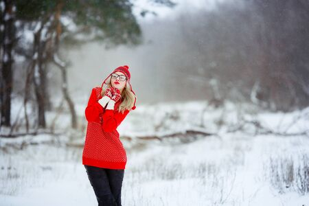 A woman in a red sweater in winter enjoys life in a snowy glade.