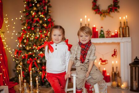 Beautiful kids brother and sister on kami background with Christmas lights and Christmas tree decorated with garland.