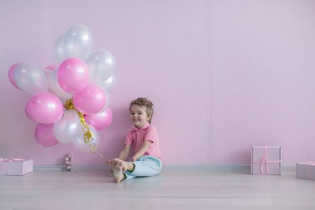 A barefoot boy at a birthday celebration sits surrounded by pink and white balloons.