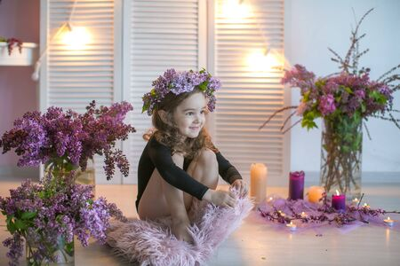 Girl child with a wreath of lilac on his head sits on the floor surrounded by a vase of flowers.
