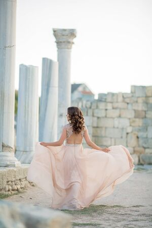 Adult woman between antique columns of architecture dressed in a long stylish light dress. Stok Fotoğraf