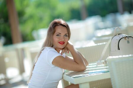 Beautiful woman smiling and sitting at a table in a cafe on the street while on vacation. Stok Fotoğraf