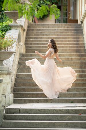 Beautiful woman on the background of steps in a beautiful wedding dress in full growth.