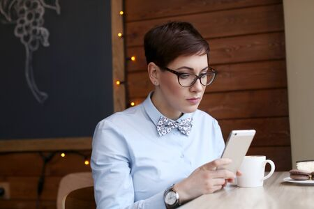 Business lady sitting in a cafe with wooden walls in a blue shirt. Stok Fotoğraf