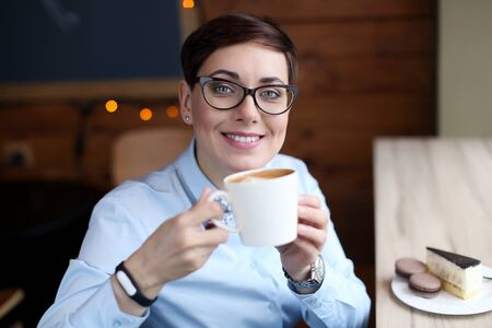 A woman with glasses and short hair a business Manager sits in a cafe near the window. Stok Fotoğraf