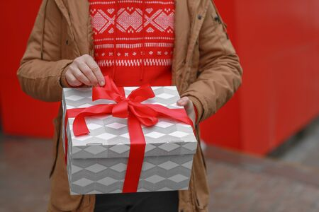 A man on a red background holds a gift box in his hands.