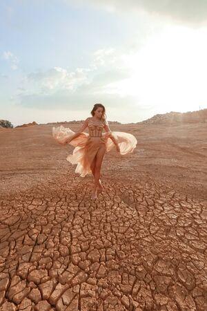 Female model in the desert in a beautiful long dress.