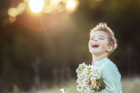 Boy blond child close up with a bouquet of daisies in his hands on a blurred background outdoors.