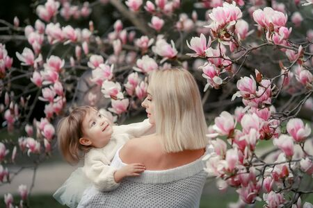 Portrait of happy joyful child in white clothes over tree flowers blossom background. Family playing together outside. Mom cheerfully hold little daughter Newborn spring concept.