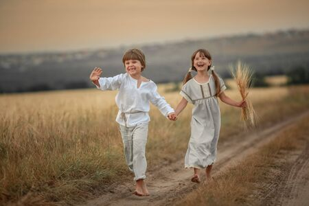 Brother and sister village children running barefoot on a rural road. Stockfoto - 135497004
