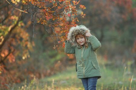 Girl child preschooler is on a green glade on the background of trees with yellow leaves.