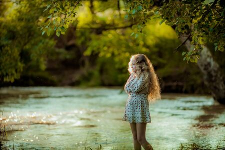 A young girl with long blond curly hair and a summer skirt poses on the Bank of the river in the spring green forest. Stockfoto