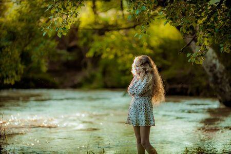 Una giovane ragazza con lunghi capelli ricci biondi e una gonna estiva posa sulla riva del fiume nella foresta verde primaverile. Archivio Fotografico