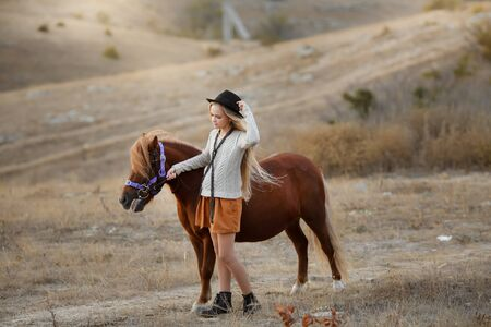 Pony or little horse riding a young female rider.