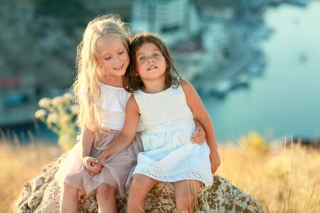Two girls 5-6 years old on a Sunny summer day on the mountain.