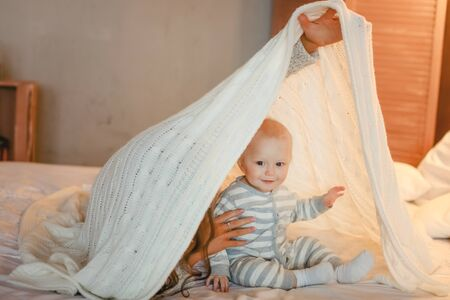 Baby and mom play on the white bed and hide under the covers. Stok Fotoğraf - 137877133