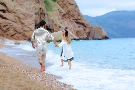 Frame shoot of couple walking on beach together in love holding each other by hand