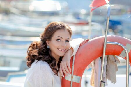 A woman a beautiful fashion model in comfortable clothes on a trip sits near a boat on the pier.