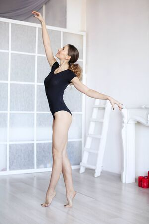 The girl performs exercises for ballerinas and stretches in the Studio.