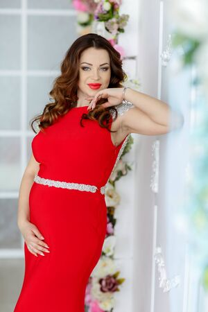 Woman 30-35 years old in a stylish red dress in pregnancy. 写真素材