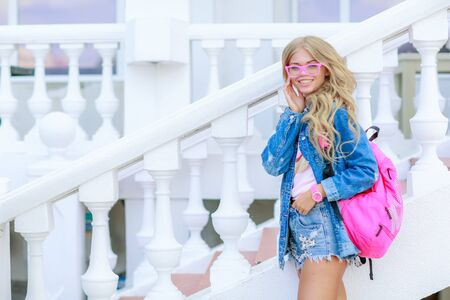 A girl with a pink backpack behind her back and in stylish denim clothes on the street.