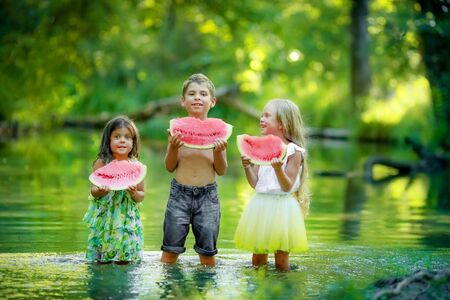 Three outdoor children stand together in the lake and hold an eraser of a juicy watermelon in their hands.