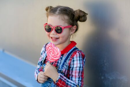 Little stylish girl in sunglasses and two pigtails on her head.