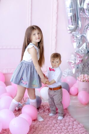 Brother and sister children on birthday in childrens room decorated with pink balloons.