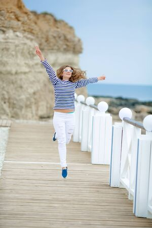 Happy dancing girl with flying red hair on city embankment, enjoy life concept. Happily laughing young woman walking on summer street