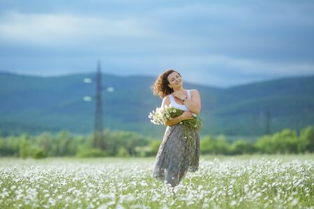 Cheerful young girl with a bouquet of flowers in the hands of outdoor. Stock fotó