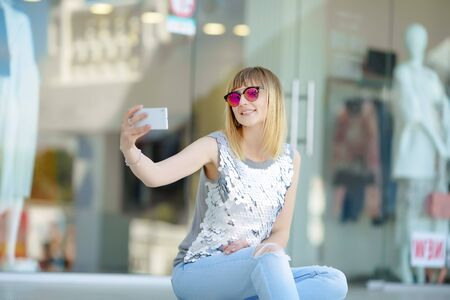 A woman with glasses holds a mobile phone and takes a selfie. Reklamní fotografie