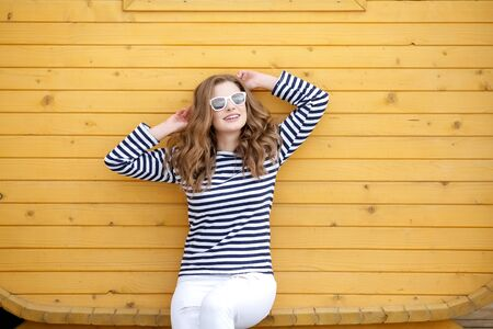 Portrait of a cute smiling girl in white jeans and a striped T-shirt near a Yellow wall.