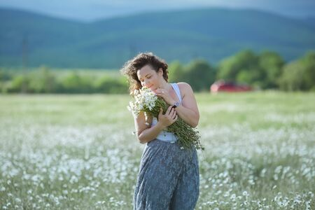Happy adult woman in a wide field with daisies.