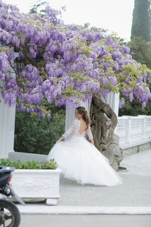 Glamorous young woman in a classic white wedding dress on a walk in the Park on her wedding day.