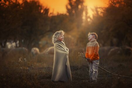 Brother and sister walking in the evening in the garden. The brother carefully covered his sister with a blanket.