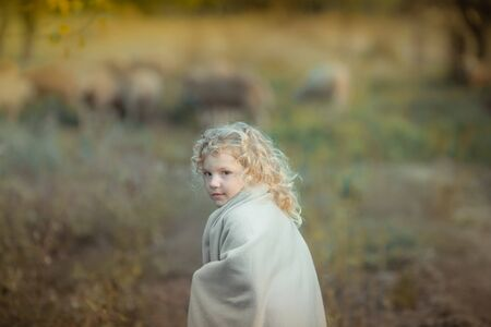 A blond curly haired girl covered with a blanket walks in a dark garden. Фото со стока
