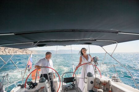 Family wedding couple on a sea voyage on a sailing yacht.