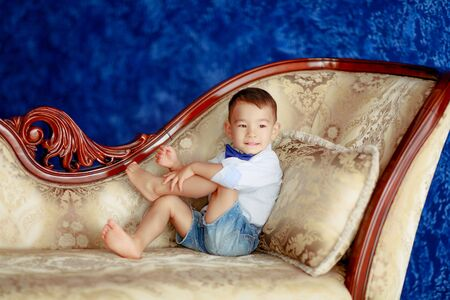 The boy 4-5 years Asian looks dressed as a gentleman and sits on the sofa. Фото со стока
