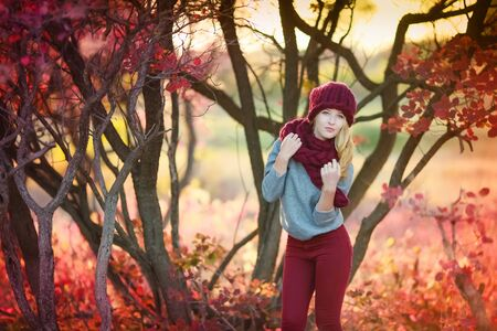 A woman walks in autumn in a public Park in a warm knitted hat and a red scarf.