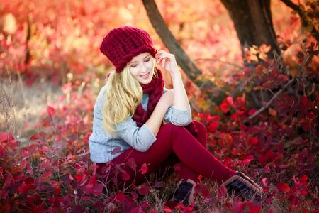 A woman in a warm knitted hat sits under a tree with fallen bright red natural leaves.