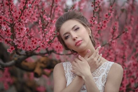 Portrait of a woman close-up on the background of cherry blossoming trees. Фото со стока