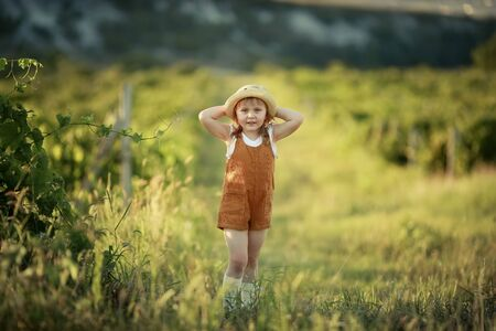 A cheerful girl in a hat walks on a young field with low green grass.