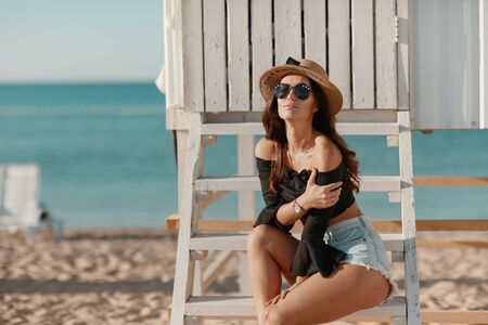 A woman sits on the sand on the beach near a white wooden fence wearing sunglasses and shorts. Фото со стока